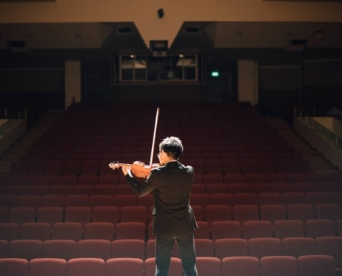 boy playing violin in recital hall